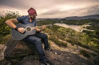 Ein junger Mann, der Gitarre spielt in freier Natur