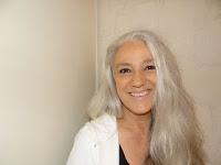 Eine junge Frau mit blonden langen Haaren, die lächelt
