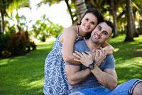 Ein junges Paar auf grüner Wiese im Wald, das sich umarmt